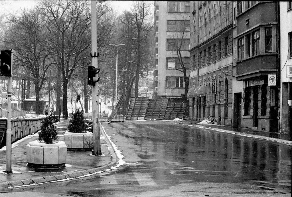 Holzabschirmungen und Bäume schützen vor den Scharfschützen beim Überqueren einer Kreuzung